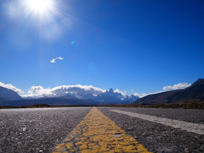 open empty road with blue skies and mountain in the distance