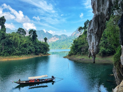 long tail boat floating on cheow lan lake with limestone cliffs in the background in khao sok