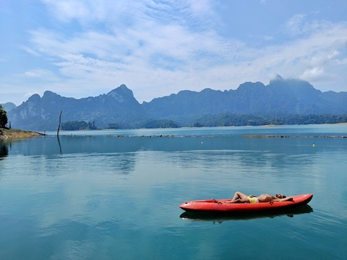 man lying in kayak in thailand is a great family vacation destination