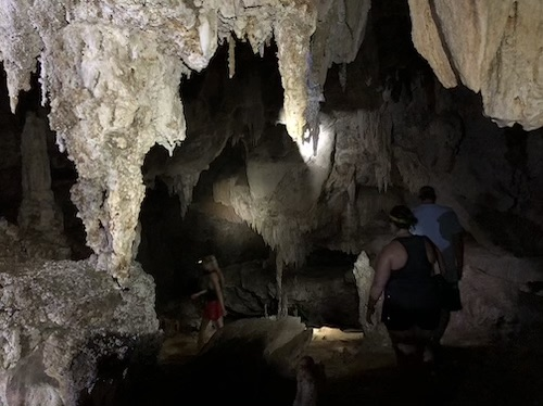 people walking inside dark cave in thailand with headlamps lighting the way