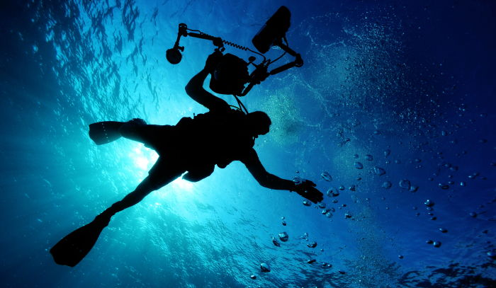 scuba diving beginner holding camera equipment close to the surface of the ocean