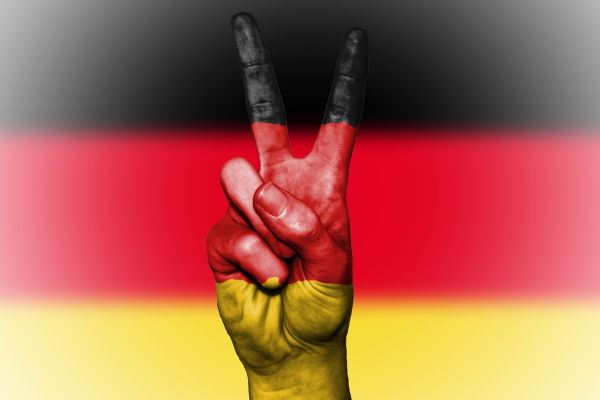 the Germany flag behind a hand painted in the Germany flag colours gesturing the piece symbol