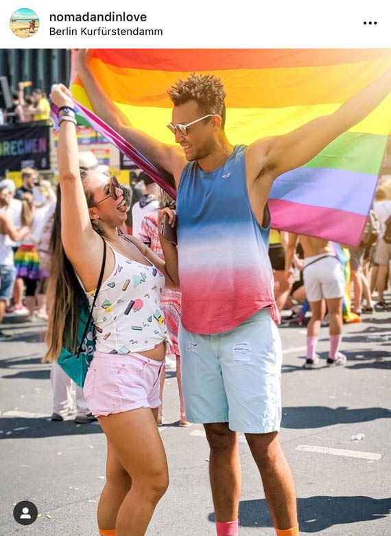street photography of an interracial couple holding up a pride flag at berlin csd festival