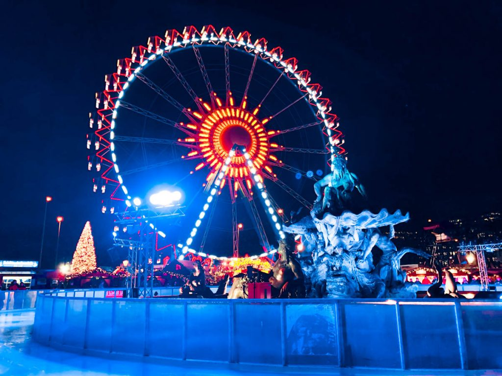 berliner wiehnachtszeit christmas market at rotes rathaus closed to alexanderplatz in berlin with huge ferris wheel, skating rink and neptune fountain in the background