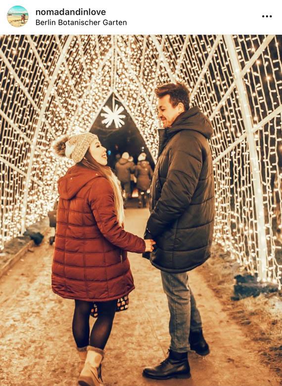 night photography of a couple walking down a tunnel of fairylights at berlin botanischer garten christmas market