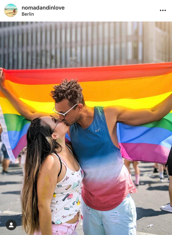 a couple kissing in front of rainbow pride flag at kurfurstendamm berlin germany gay pride festival
