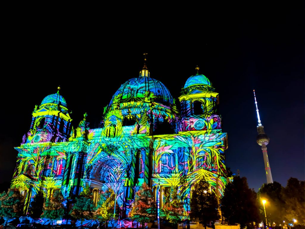 festival of lights in berlin with facade of berliner dom lit up in many colours