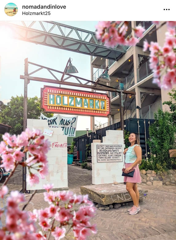 a woman standing in front of a popular flea market in berlin, holzmarkt with pink cherry blossoms framing the photo