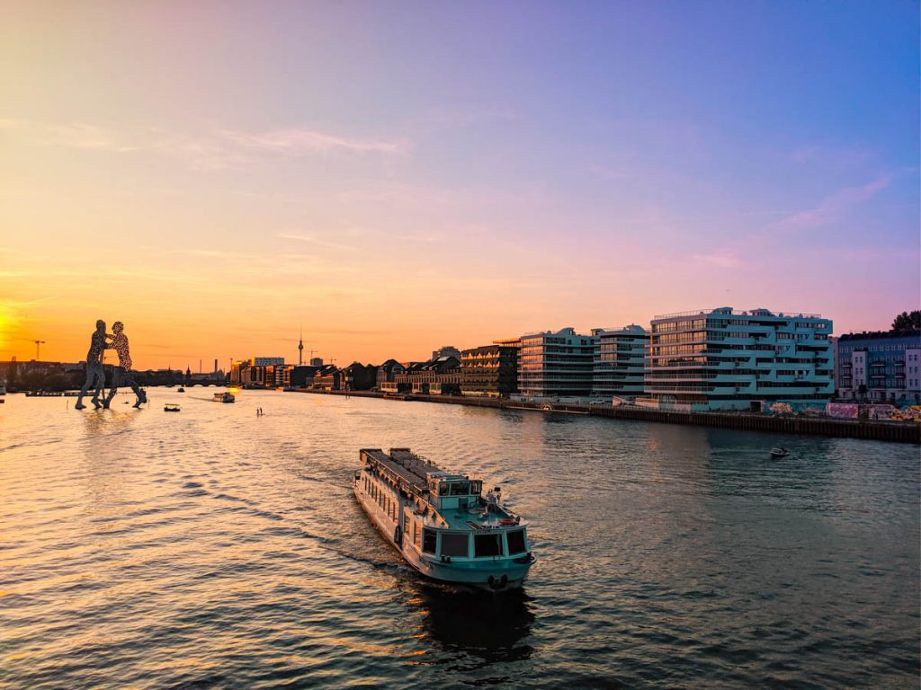sun setting over the spree river with molecule man sculpture in the background - one of the pros of living in berlin