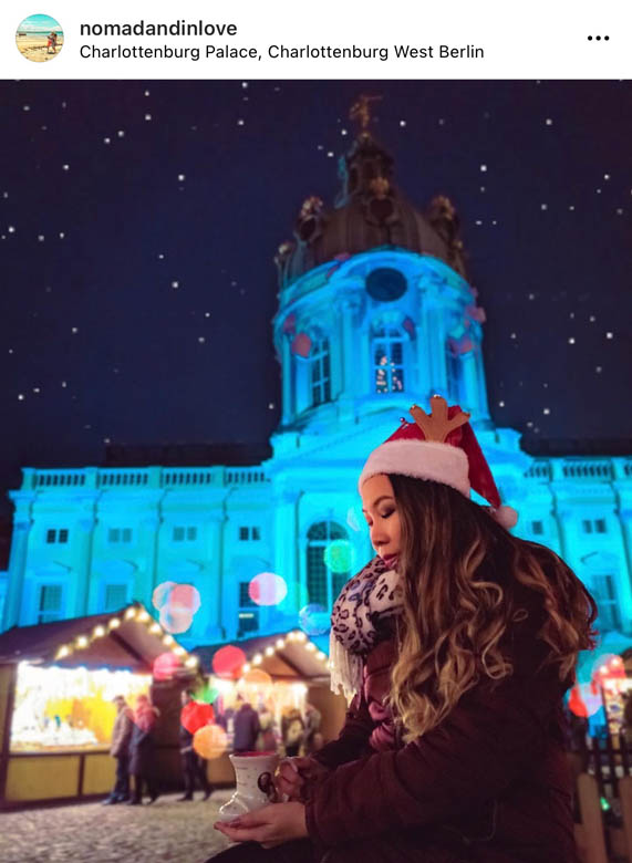 photography of a woman holding a christmas mug in front of charlottenburg christmas market in berlin