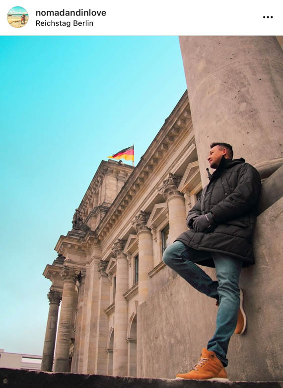 a secret photo spot at the reichstag building in berlin with a german flag against a blue sky