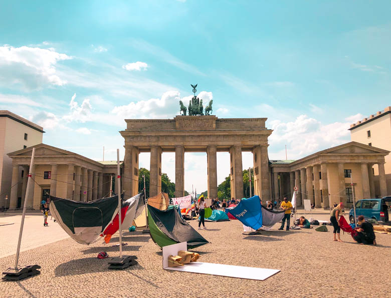 iconic Brandenburg tor in berlin whilst traveling during covid is empty as a protest is held here
