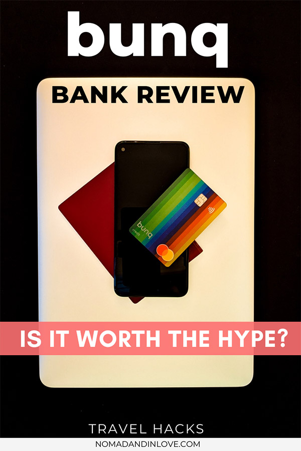 a pinnable image of bunq's mobile banking experience review containing the rainbow bunq bank debit card placed onto of a black mobile phone, which is placed on top of a maroon passport, which is placed on top of silver laptop