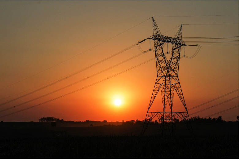 electricity power lines with orange sunset in the background
