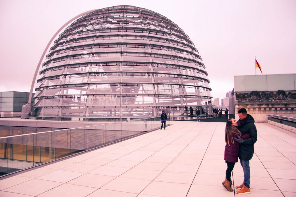 an expat couple standing on the roof of reichstag parlimentary building in berlin with glass dome in the background