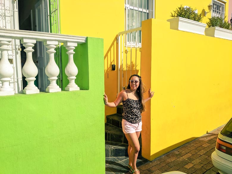 woman standing in front of colourful houses in bokaap cape town