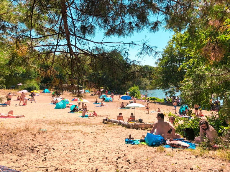 lots of people sitting on a sandy beach at flakensee lake near berlin