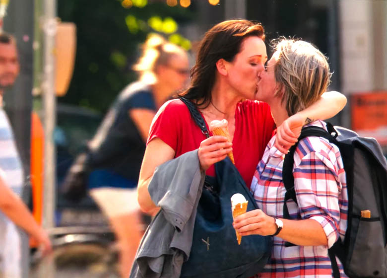 lesbian couple kissing with ice cream in hand in berlin capital of germany