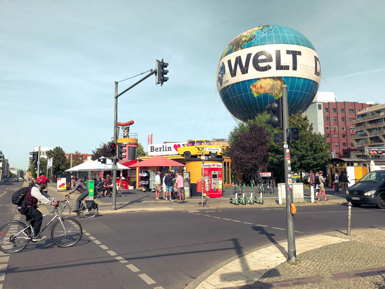 man cycling with helmet on in germany with berlin currywurst and welt balloon in the background