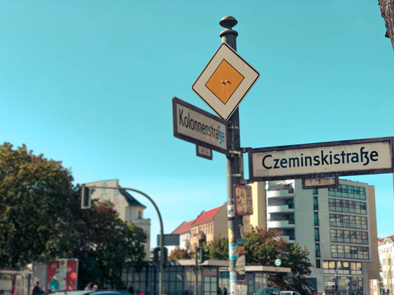 yellow and white priority road sign at the corner of kolonnenstrasse and czeminskistrasse in berlin