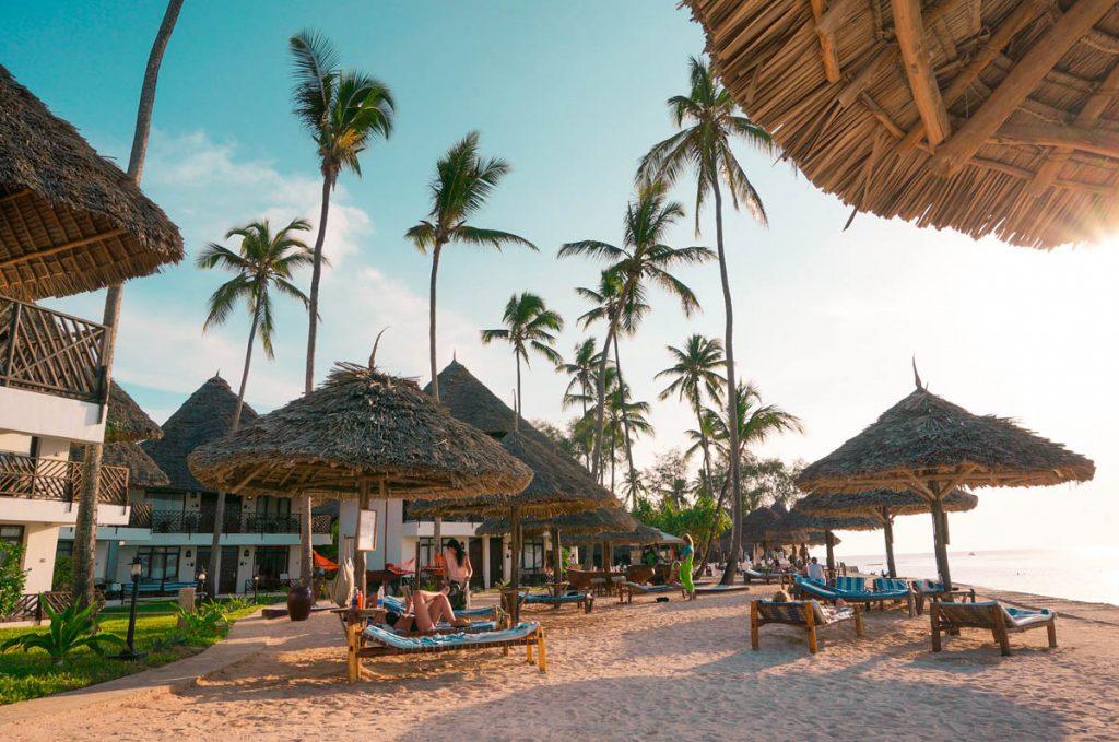 beach umbrellas and sun beds at an all inclusive resort on zanzibar beach