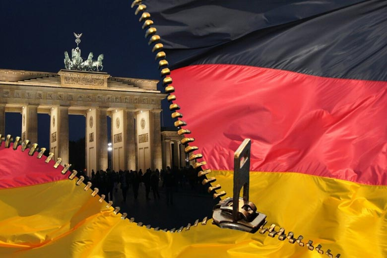 german flag in front of brandenburg gate in berlin