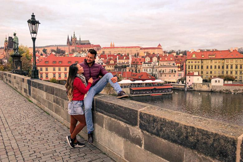 a couple sitting on charles bridge in prague