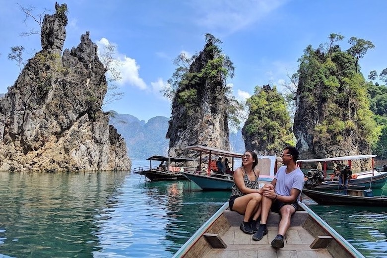 couple sitting on long tail boat on cheow lan lake in thailand