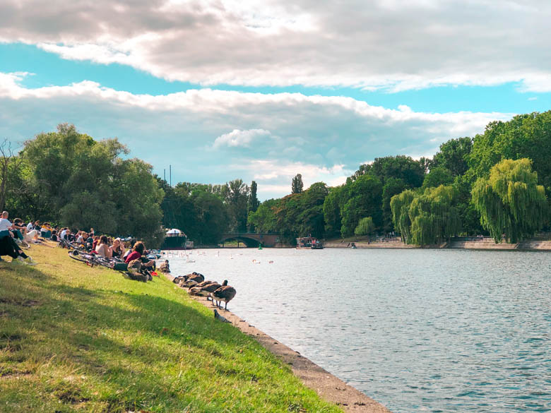 landwehr canal is a popular outdoor thing to do in berlin especially during coronavirus pandemic with people sitting on the grass overlooking the canal