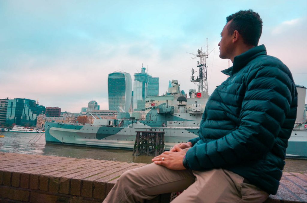 man looking across thames river contemplating the costs of living in London
