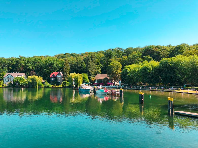 leisure yachts floating on top of a clear lake in Germany with houses and trees lining the edges at Schleuse Woltersdorf