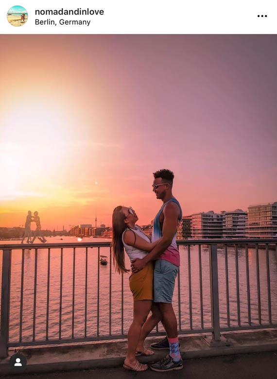 pink and orange sunset photography of a couple taken on elsen bridge in berlin germany