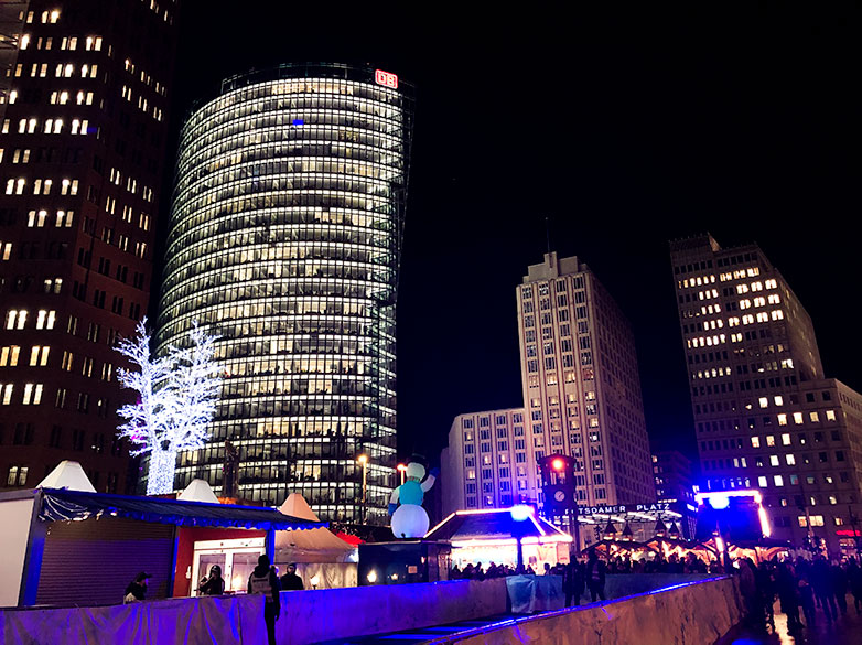 winter world at potsdamerplatz christmas market in berlin with deutsche bahn office building in the background