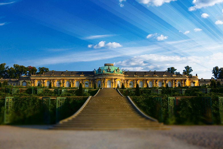 sanssouci palace or schloss sanssouci in sanssouci park during summer with sun rays in the blue sky