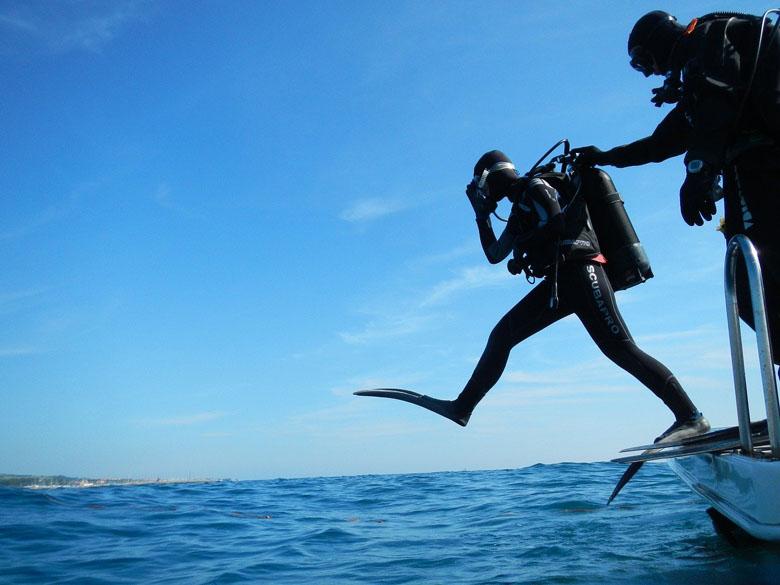 scuba diving dressed in full scuba dive gear entering the ocean using giant step technique