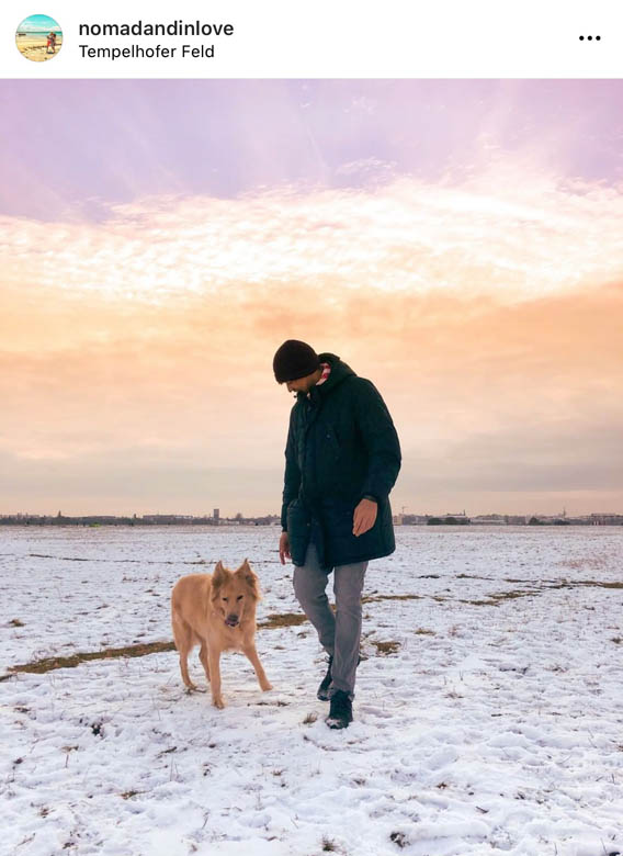 sunset photography at tempelhofer feld in berlin with a man walking a dog in the snow