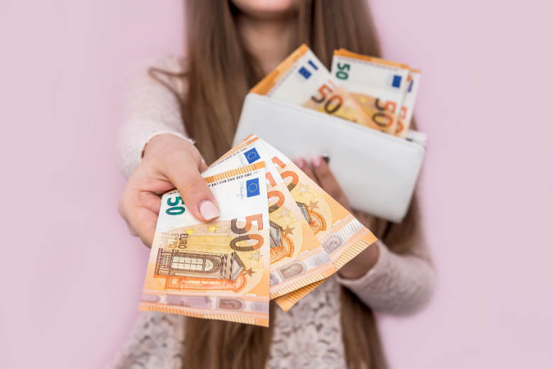 woman holding lots of €50 notes against a pink background