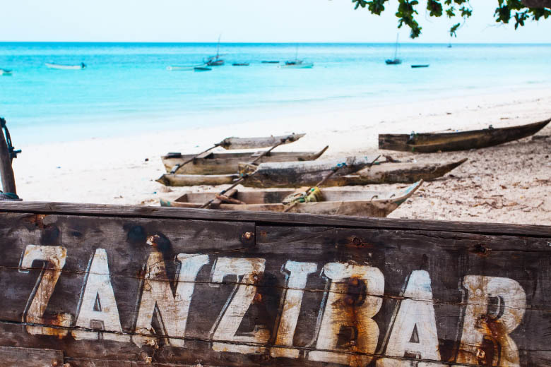 wood boats lying on the beach in zanzibar with turquoise blue ocean in the background