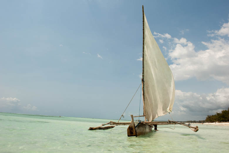 a traditional dhow boat in zanzibar with a white sail floating on crystal clear waters